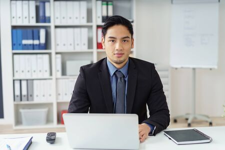 young executive: Handsome calm Asian executive man in office sitting up in front of his laptop at desk with phone and spiral notebook