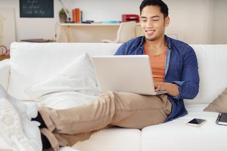 trabajando en casa: Joven hombre asiático pasar un día de relax en casa con los pies en un sofá navegando por internet en un ordenador portátil con una sonrisa Foto de archivo