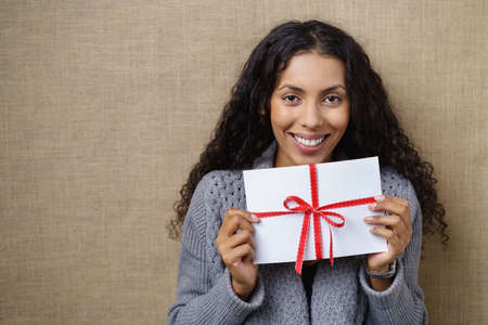 Waist Up of Smiling Young Woman with Curly Dark Hair Looking Excited and Holding White Envelope Wrapped with Red Ribbon and Bow in Studio with Textured Beige Background and Copy Space Stock Photo