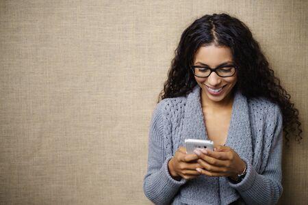 腰のプロ居心地の良い灰色のセーター カーディガンを身に着けている若い女性の笑顔と質感のベージュ色の背景とコピー スペースとスタジオで携帯