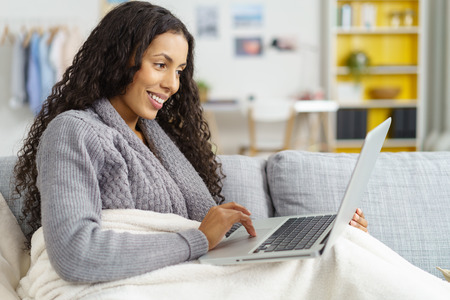 american media: Happy young woman relaxing at home wrapped in a warm blanket on the sofa surfing the internet on her laptop computer with a smile of pleasure