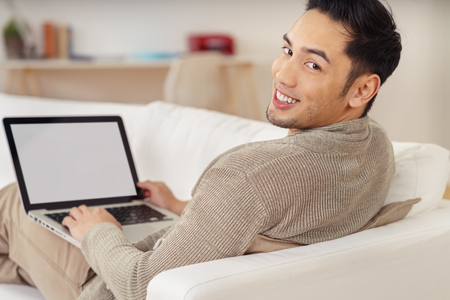 Красивый молодой человек Азии с милой улыбкой, расслабляющий на диване у себя дома со своим ноутбуком оглядываясь на камеру, пустой экран на компьютере видимым