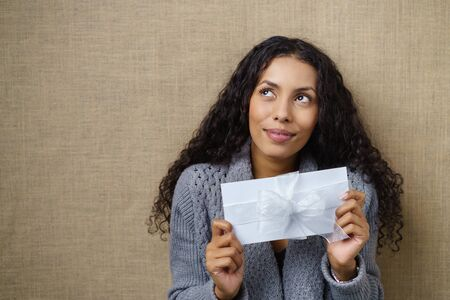 Waist Up of Smiling Young Woman with Curly Dark Hair Looking Excited and Holding White Envelope Wrapped with white Ribbon and Bow in Studio with Textured Beige Background and Copy Space Stock Photo