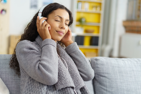 hobbies: Blissful attractive trendy young woman enjoying her music as she relaxes on a sofa in her living room listening to tunes on her headphones with her eyes closed smiling with enjoyment