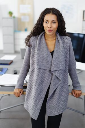 self assured: portrait of a confident, successful business woman standing in the office in front of her desk