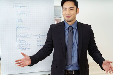 executive courses: Single confident young Asian male salesman in suit and tie standing with wide open arms in front of a chart and big smile Stock Photo