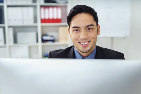 businessman working at his computer: Friendly successful Asian businessman sitting working at his desk in the office smiling over his computer at the camera