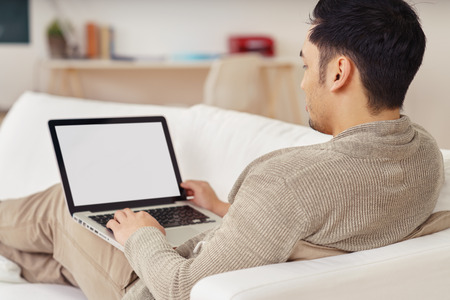 Young man working on a blank laptop with the screen visible to the camera as he reclines on a comfortable sofa at home, rear over the shoulder view