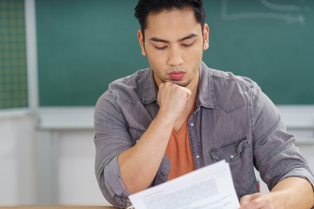 Attractive young male Asian student or teacher reading class notes in front of the blackboard with a thoughtful expression