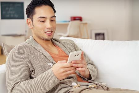 Jonge Aziatische man ontspannen thuis controleren voor tekstberichten op zijn mobiele telefoon met een glimlach Stockfoto