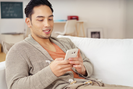 the guy: Young Asian man relaxing at home checking for text messages on his mobile phone with a smile