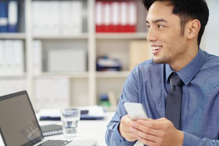 asian business man: Happy Asian businessman holding a mobile phone in his hand as he looks across the office with an excited smile, close up view Stock Photo