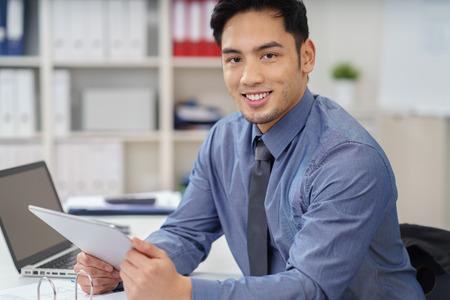 Glimlachende Aziatische zakenman werken in een kantoor zittend aan een bureau met een tablet in zijn hand glimlachen naar de camera