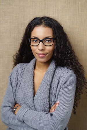 waist up: Waist Up of Confident Businesswoman Wearing Eye Glasses and Cozy Gray Sweater Standing in Studio with Arms Crossed in front of Textured Beige Background