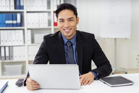 hombre de negocios joven linda con la perilla que miran por delante por detrás de la computadora portátil en el escritorio en la oficina con la expresión feliz