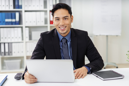 Cute young businessman with goatee looking ahead from behind laptop at desk in office with happy expression