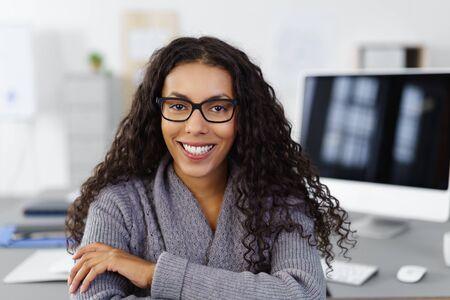 ritratto di una donna d'affari con i capelli neri arricciati seduta alla sua scrivania sorridendo alla telecamera
