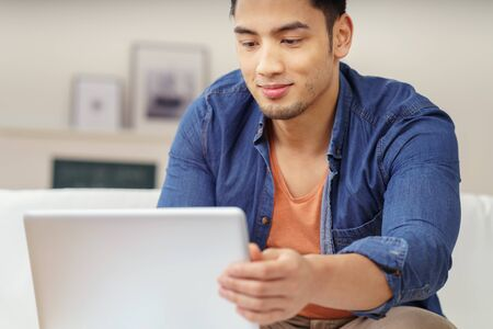 personas pensando: Hombre asiático joven que se sienta en un sofá en la lectura de la información en casa en su computadora portátil con una sonrisa tranquila, cerca vista superior del cuerpo