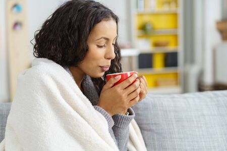 energising: Cold young woman enjoying a mug of hot winter coffee as she snuggles up in a warm rug on her sofa at home, close up side view