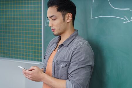 young male: Young Asian male student checking his mobile phone for text messages as he leans against the blackboard in the classroom, side view Stock Photo