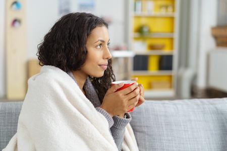 Atractiva joven relajante en casa en invierno acurrucarse en el sofá envuelto en una manta caliente sosteniendo una taza de café caliente en sus manos