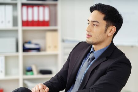 success man: Young Asian businessman relaxing back in his chair in the office watching something to the left of the frame with a thoughtful expression