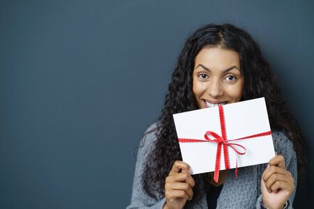 generous: woman holding envelope wrapped with a red bow and ribbon in front of her face