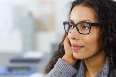 confident business woman: profile of a beautiful woman wearing glasses with hand on her chin looking to a side in thoughts