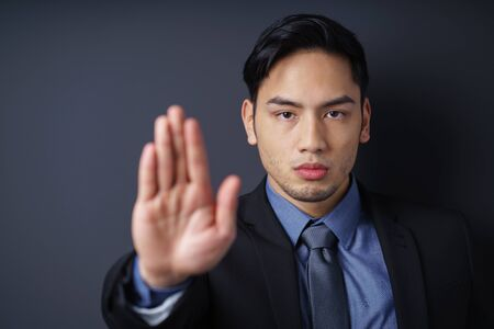 security company: Stern Asian man giving a halt or stop gesture raising the palm of his hand, head and shoulders with focus to his face