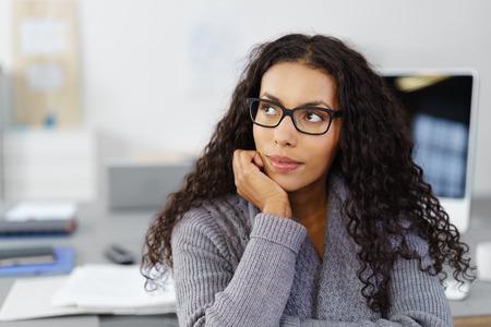 деловая женщина сидела за столом в офисе с ее подбородок на ее руку, глядя вверх в мысли