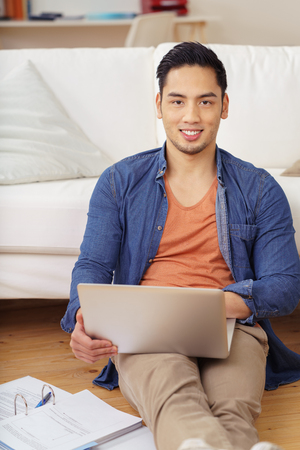 Friendly young Asian student studying at home sitting on the floor leaning on the sofa with his laptop computer and notes smiling at the camera