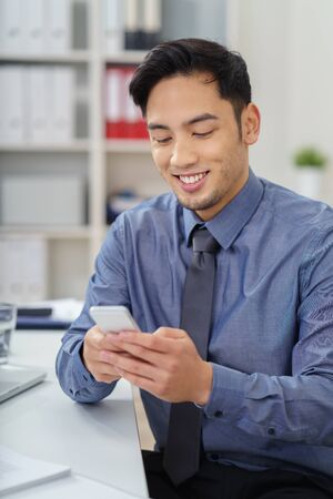 using phone: Pleased attractive young Asian businessman reading a text message on his mobile phone with a smile in the office
