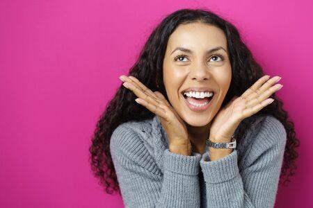 éxtasis: mujer hispana emocionados con las manos en la mejilla sobre color de rosa Foto de archivo
