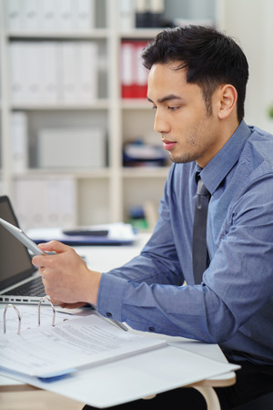 businessman working at his computer: Asian businessman working at his desk in the office reading information on a tablet, computer with a serious expression Stock Photo