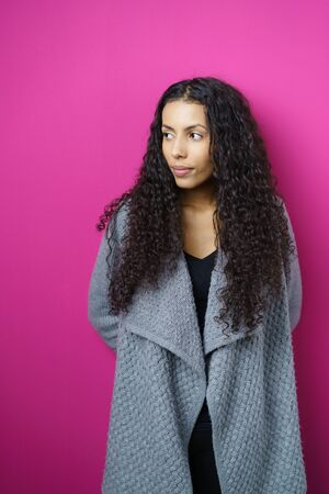 expressionless: Waist Up of Young Woman with Long Curly Hair Wearing Cozy Gray Sweater and Looking to the Side with Serious Expression in Studio with Fuchsia Background and Copy Space