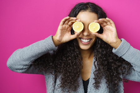 up view: Head and Shoulders of Playful Smiling Young Woman with Long Curly Hair Holding Slices of Lime Citrus Fruit in front of Eyes in Studio with Fuchsia Background and Copy Space Stock Photo