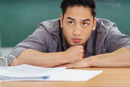 adult student: Thoughtful Asian student watching the lecture leaning forwards on his desk with his chin on his hands, close up front view Stock Photo