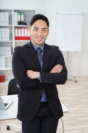 Confident smiling Asian businessman standing in the office with folded arms, conceptual of leadership and management