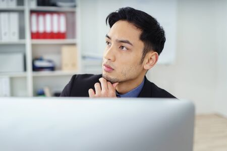 deep thought: Calm young Asian corporate executive in front of computer monitor with fingers on chin in deep thought Stock Photo