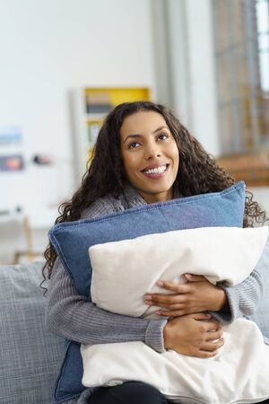 encouraged: happy woman sitting at home on her couch, smiling and embracing pillows