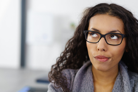 cabello rizado: Cabeza y hombros de primer plano de mujer de negocios joven lleva gafas y mira para arriba en pensamiento en la Oficina con copia espacio - Perplejos El pensamiento de negocios Foto de archivo