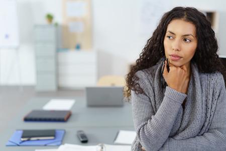 zakenvrouw met de hand op de kin zit aan bureau in het kantoor in gedachten