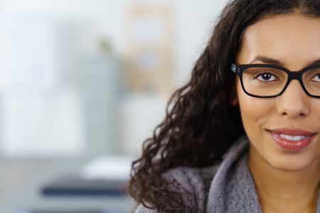 Head and Shoulders Close Up of Young Woman Wearing Eye Glasses in Office with Copy Space - Intelligent Businesswoman Smiling at Camera