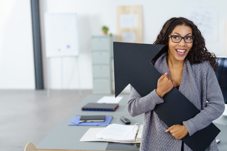 exultant: happy business woman with spectacles holding black arrow, conceptual for career or education