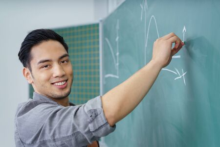 asian adult: Smiling confident young Asian university student writing on a green chalkboard in the lecture hall or classroom turning to smile at the camera