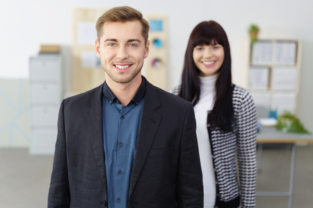 charismatic: Confident smiling manager or team leader standing in the office looking at the camera with an attractive female colleague in the background