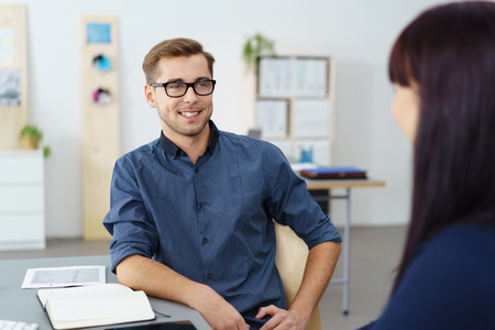 chats: Handsome confident young businessman in glasses leaning back relaxing in his chair as he chats to a female colleague Stock Photo
