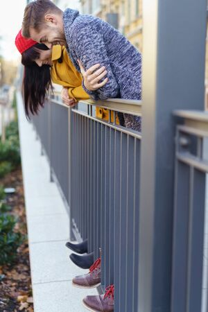 bannister: Young couple having fun outdoors balancing on a metal railing on a walkway looking down at their toes poking through the bars with a smile Stock Photo