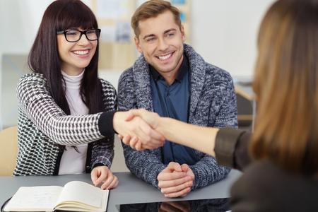 Пара рукопожатием с брокером или страховым агентом в ее офисе, счастливо улыбается, как они закрывают сделку Фото со стока