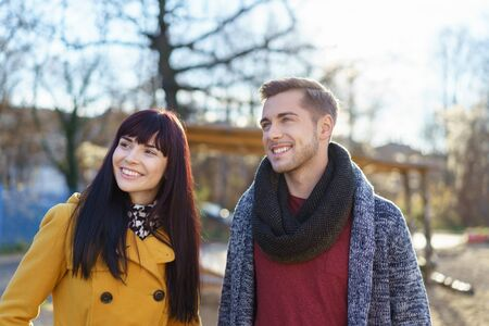 Happy trendy young couple in winter fashion standing watching something outdoors to the left of the frame and smiling